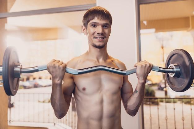 Atletische man voert training barbell op te heffen
