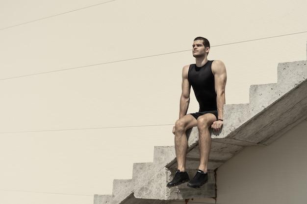 Atletische man zit op stijgende betonnen trappen