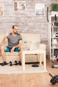 Atletische man zwaaiend naar zijn personal trainer tijdens online training in tijd van wereldwijde pandemie.