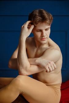 Atletische mannelijke balletdanser, dansstudio, blauwe muur en rode doek. performer met gespierd lichaam, gratie en elegantie van bewegingen