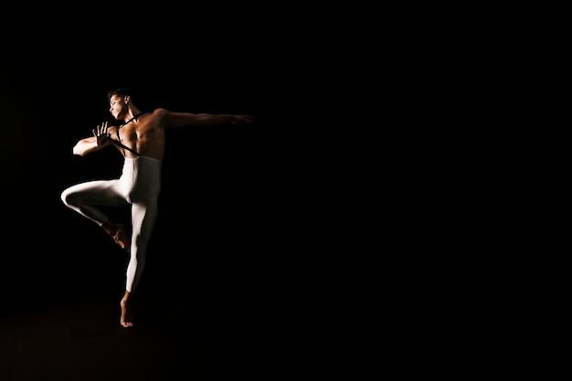 Atletische mannelijke danser die op zwarte achtergrond danst