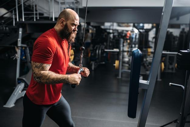 Atletische mannelijke persoon, training op hometrainer