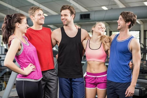 Atletische mannen en vrouwen die bij crossfitgymnastiek stellen