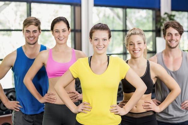 Atletische mannen en vrouwen die bij gymnastiek stellen