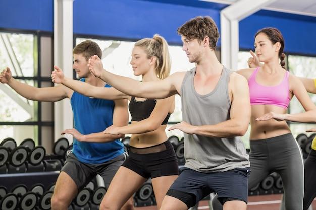 Atletische mannen en vrouwen die bij gymnastiek uitwerken