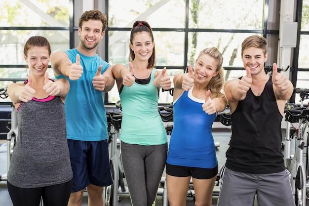 Atletische mannen en vrouwen die met duimen omhoog bij gymnastiek stellen