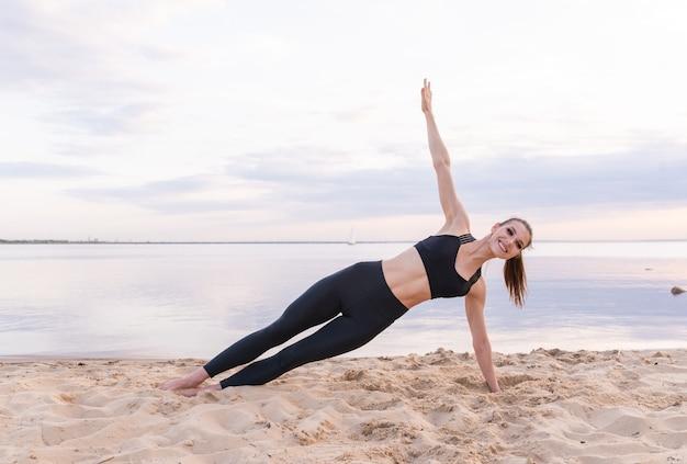 Atletische meisje doet fitness yoga aan zee