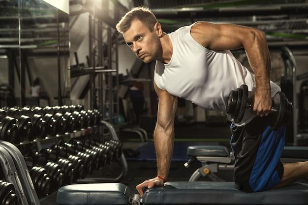Atletische mens die bij het gymnastiekgewichtheffen uitoefenen die de oefening van de tricepsdeadlift met domoren doen