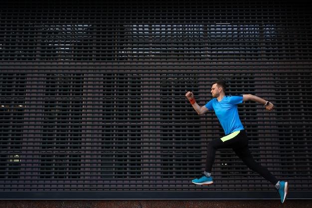 Atletische mens die bij stedelijke straat tegen grijze achtergrond loopt