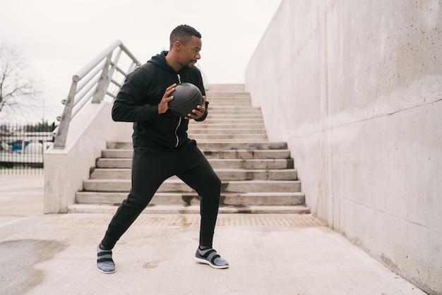 Atletische mens die de oefening van de muurbal doet.