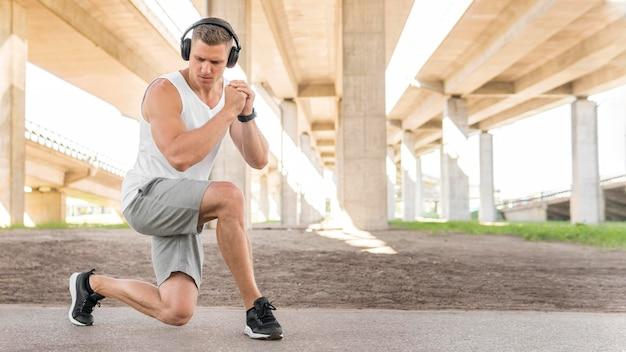 Atletische mens die zich in openlucht met exemplaarruimte uitrekken