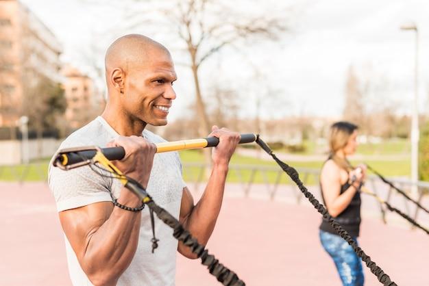 Atletische mensen trainen met een elastische gymstok in het park. focus op sportman. multi-etnische mensen die buiten sporten.