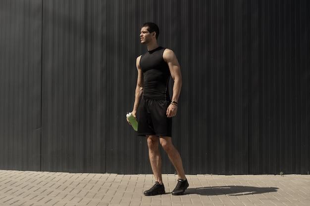 Atletische moderne jonge man die zich voordeed op een grijze metalen muur