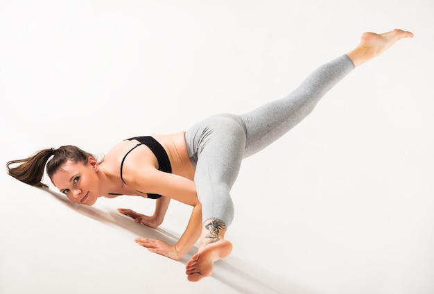 Atletische mooie jonge slanke vrouw doet geavanceerde houding op een tapijt op de vloer op een wit oppervlak