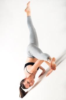 Atletische mooie jonge slanke vrouw doet geavanceerde houding op een tapijt op de vloer op een witte achtergrond. yoga leraar concept. advertentie ruimte