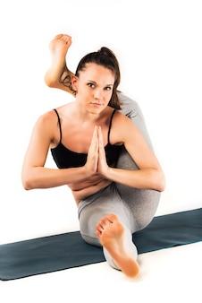 Atletische mooie jonge slanke vrouw doet geavanceerde houding op een tapijt op de vloer op een witte muur