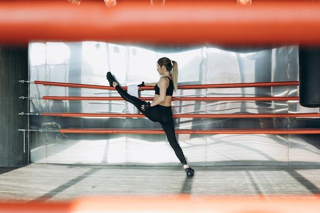 Atletische mooie vrouw doet push-ups als onderdeel van haar cross fitness, bodybuilding gym