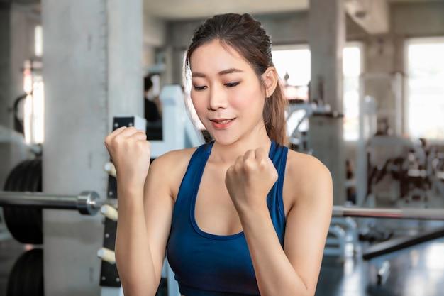 Atletische mooie vrouw fit en gezond lachend in de sportschool na training.