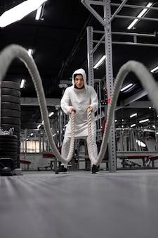 Atletische moslimvrouw trainen met touwen bij crossfit sportschool copyspace vertrouwen motivatie sport levensstijl activiteit hobby gezonde krachtige vrouwelijkheid trainingsconcept
