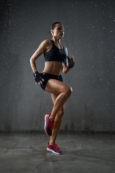 Atletische natte vrouw die ter plaatse loopt
