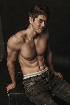 Atletische schattige man poseren topless in spijkerbroek.