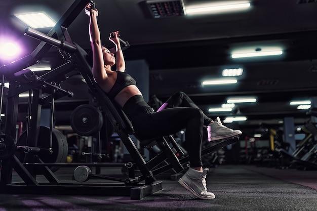 Atletische sexy vrouw die oefening doet die machine in gymnastiek gebruikt