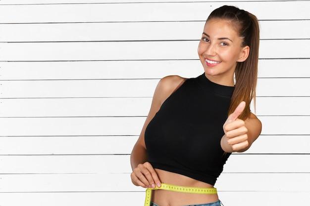 Atletische slanke vrouw die haar taille meet door maatregelenband