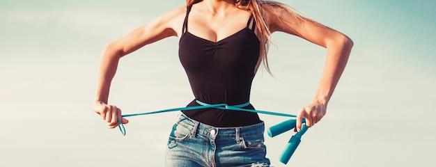 Atletische slanke vrouw die haar taille meet door meetlint na dieet.