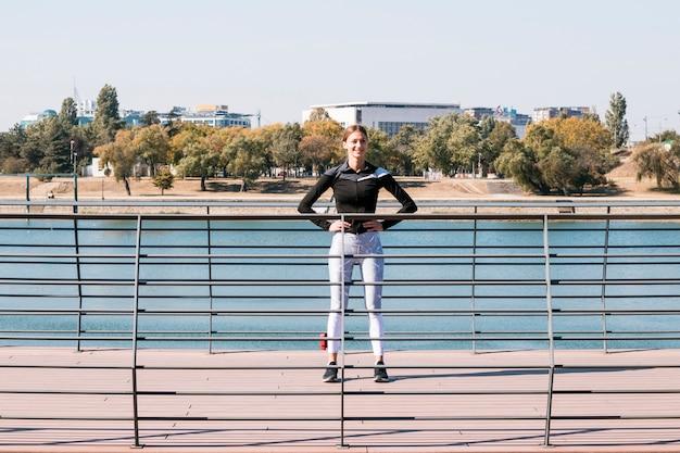 Atletische sportvrouw die zich achter het traliewerk dichtbij het meer bevindt