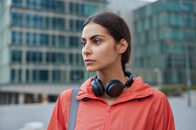 Atletische sportvrouw poseert op straat in sportkleding draagt sportfaciliteiten om buiten te rusten rust na dagelijkse training verbetert fysiek haar gezondheid staat tegen wazig