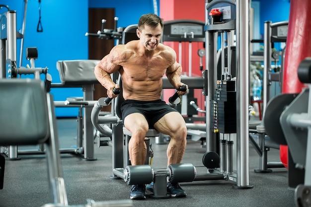 Atletische sterke bodybuilder uitvoeren oefening in sporthal op de ongelijke staven