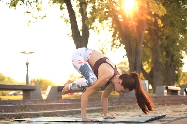 Atletische sterke vrouw die moeilijke yoga beoefent, stelt buitenshuis.