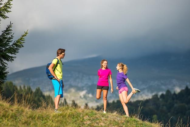Atletische trainer in de natuur strekt zich uit tot twee meisjes