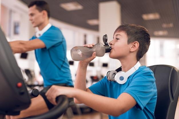 Atletische vader en zoon doen oefeningen in de sportclub