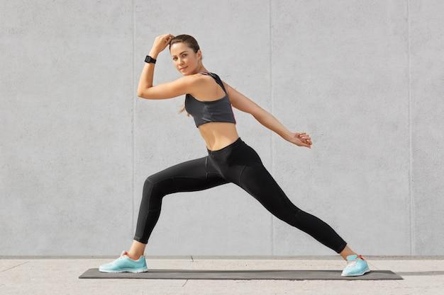 Atletische vrouw beoefent yoga, maakt brede passen, toont goede flexibiliteit, poseert tegen grijs