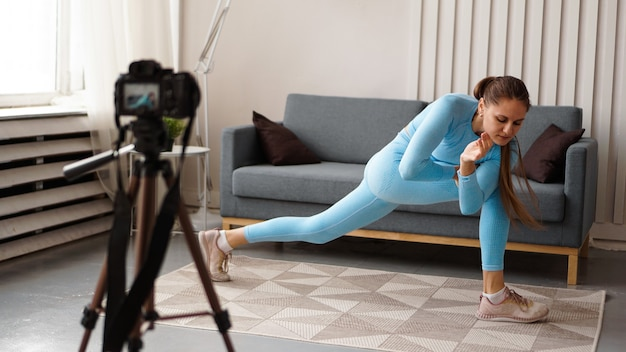 Atletische vrouw blogger in sportkleding schiet video op camera thuis in de woonkamer. sport- en recreatieconcept. gezonde levensstijl.