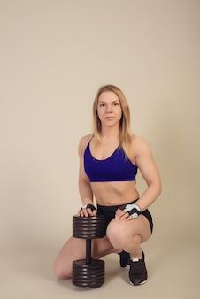 Atletische vrouw bodybuilder zit met een zware halter