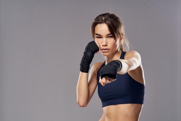 Atletische vrouw bokstraining oefeningen fitness poseren donkere achtergrond