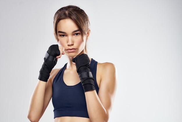 Atletische vrouw bokstraining ponsen oefening lichte achtergrond