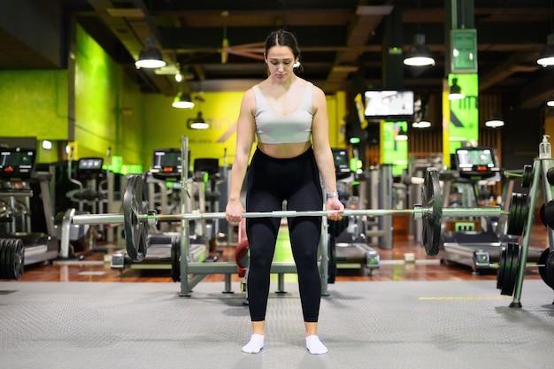 Atletische vrouw deadlift uitoefenen in een sportschool.