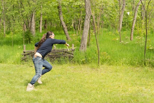 Atletische vrouw die badminton speelt op een met gras begroeide