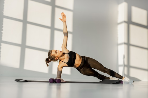 Atletische vrouw die binnenshuis fitness doet