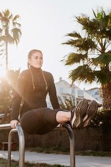 Atletische vrouw die buiten uitoefent