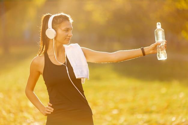 Atletische vrouw die een fles water aanbiedt
