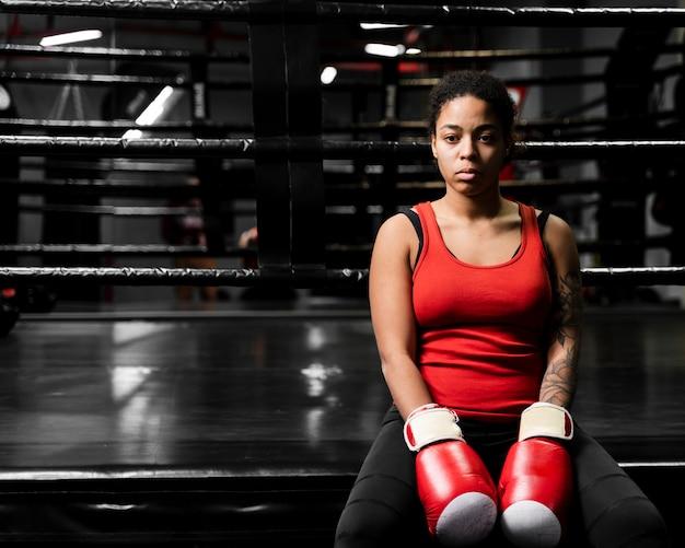 Atletische vrouw die een onderbreking van het uitoefenen neemt