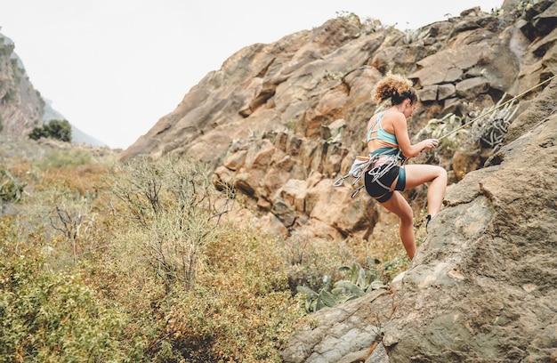Atletische vrouw die een rotsmuur beklimt