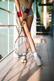 Atletische vrouw die een tennisracket in een tennisbaan houdt