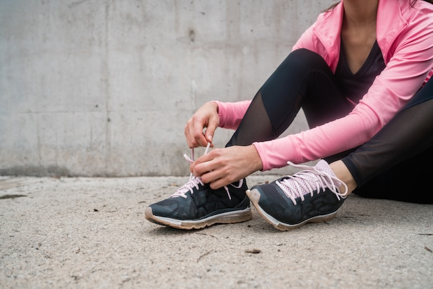 Atletische vrouw die haar schoenveters bindt.