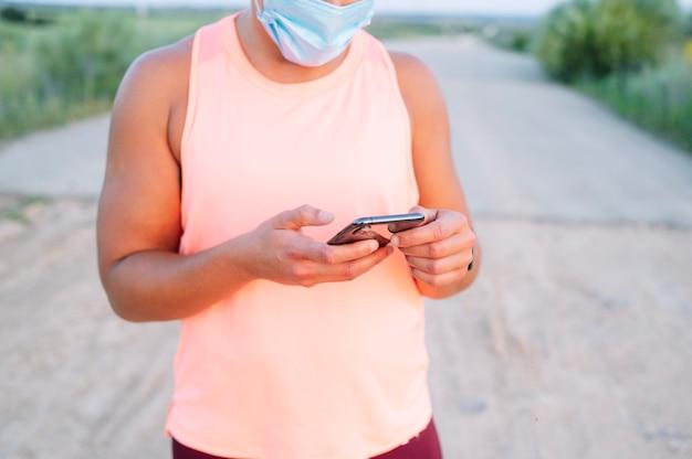 Atletische vrouw die haar smartphone met gezichtsmasker buitenshuis gebruikt