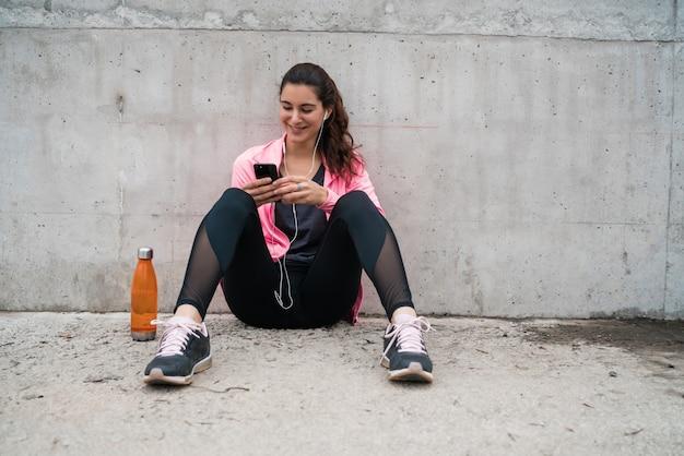 Atletische vrouw die haar telefoon met behulp van.